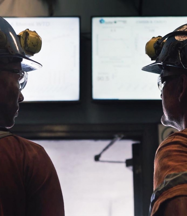 Frontline personnel at Centennial Coal Springvale Mine discuss KPIs from Pulse Analytics as displayed on large TV screens